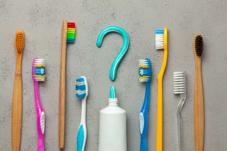 Question mark from toothpaste. The concept of choosing good toothpaste for teeth whitening. Tube of colored toothpaste and toothbrush on Gray background. Copy space for text