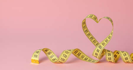 Yellow measuring tape in the shape of a heart on a pink background. The concept of weight loss for the normal functioning of the heart and body. Copy space for text