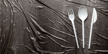 Plastic cutlery, forks, spoons and knives. Pollution of the environment with plastic and microplastics. Black plastic background. Copy space for text