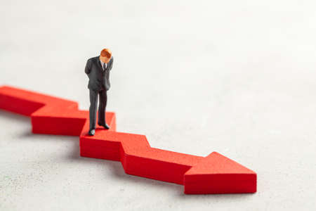 Figurine of a businessman in a suit and tie and a red down arrow. The concept of bankruptcy, falling profits and reducing indicators, analysis of losses. Copy space for text.