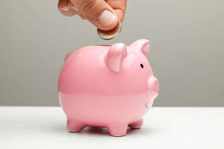 Pink piggy bank and coin in a male hand on a gray background. Imagens