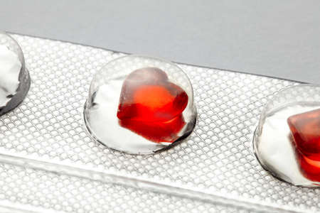 Love pills. Blister pack with red heart shaped pills. Tablets for lovers or potency. Gray background