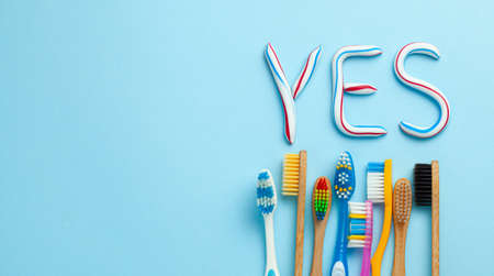 Word YES from toothpaste. Tube of colored toothpaste and toothbrush on blue background. The concept of proper cleaning and care of teeth. Copy space for text.