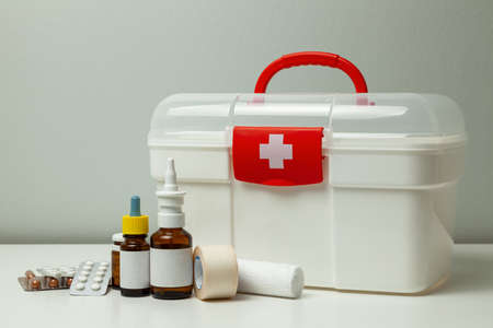 First Aid Kit. White box with a cross and a red fastener and pills with medicine bottles on a gray background Stock fotó