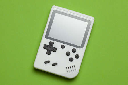 Old game console. Gamepad is white on a green background.