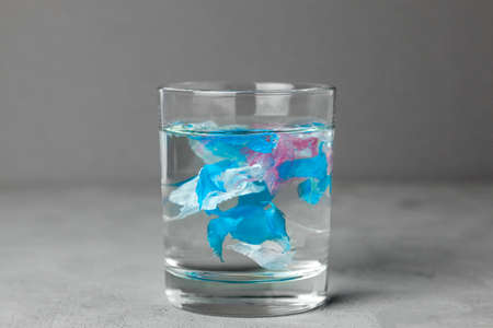 Microplastic. Water pollution by small particles of plastic. Glass of water with plastic.