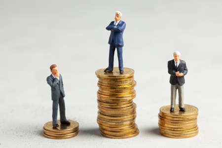 Successful businessman with big profits on stack of gold coins and less successful businessmen with small companies. Adequate investment in the company