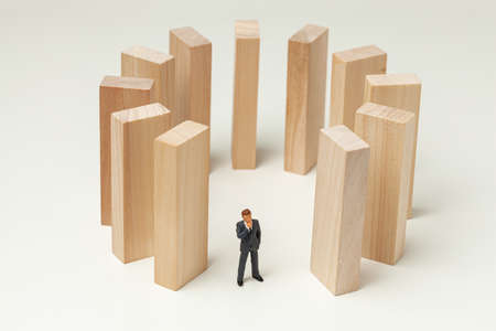 Karma like falling dominoes. Businessman pushed dominoes and expects and analyzes the result. Dangerous situation.