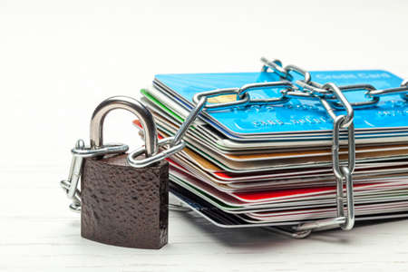 Stack of credit cards and a padlock with chain isolated on a white background. Closed access to credit cards, blocked, lock.