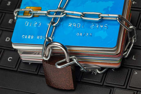 Closed access to credit cards, blocked, lock. A stack of credit cards and a padlock with a chain on a laptop keyboard.