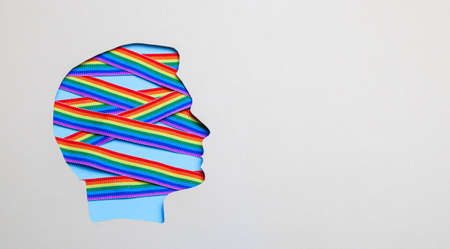 Silhouette of a male head and rainbow ribbons of LGBT pride. Gay in the head inside. Copy space for text