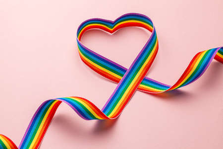 LGBT rainbow ribbon in the shape of heart. Pride tape symbol. Pink background. Banco de Imagens
