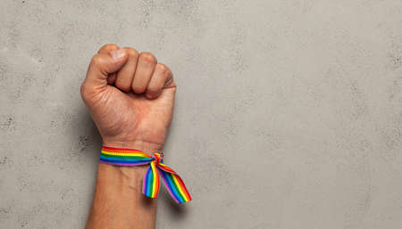 LGBT rainbow ribbon on hand with fist. Grey background. Archivio Fotografico