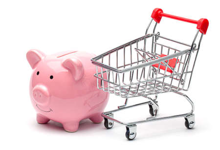 Pink piggy bank and shopping cart isolated on a white background. The concept of saving money on shopping in the store