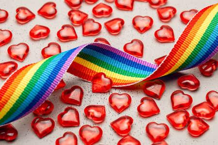 LGBT rainbow ribbon and hearts. Pride tape symbol. Grey background.