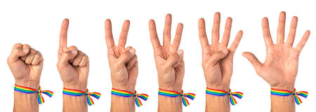 Man shows the numbers on his fingers, one, two, three, four, five. Pride male hand with rainbow LGBT tape. Isolated on a white background.