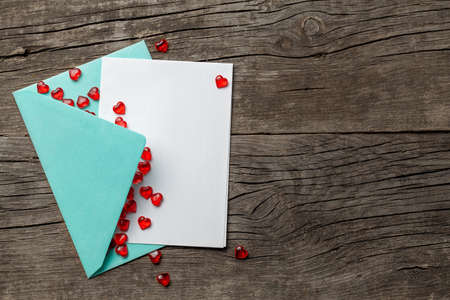 Love letter with red hearts. Blank template with place for text on postcard. Green envelope on old wooden background. mock-up.