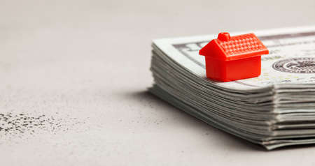 Red house on a stack of money. The concept of buying or selling real estate. Copy space for text Banco de Imagens