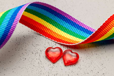 LGBT rainbow ribbon and two hearts. Pride tape symbol. Grey background.