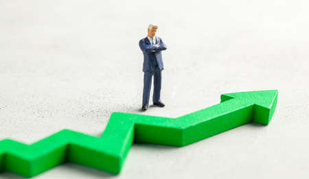 Figurine of a businessman in a suit and tie and a green up arrow. The concept of success, profit growth and an increase in performance.