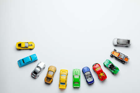 Many colored little toy cars on a gray background
