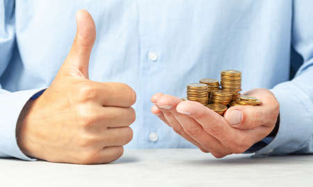 Businessman in blue shirt holds in his hand lot of coins. Positive thumbs up, like Banco de Imagens
