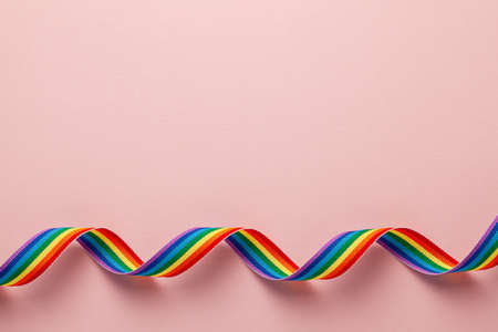 LGBT rainbow ribbon pride tape symbol. Pink background. Copy space for text Banco de Imagens