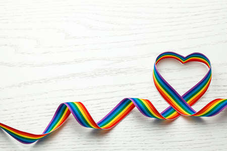 LGBT rainbow ribbon in the shape of heart. Pride tape symbol. White wood background. Copy space for text
