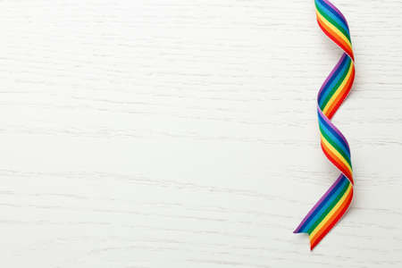 LGBT rainbow ribbon pride tape symbol. White wood background. Copy space for text