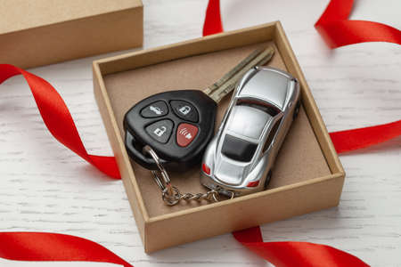 Car keys with remote control security and car key chain red ribbon and gift box.