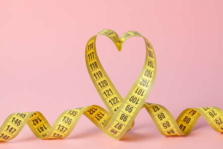 Yellow measuring tape in the shape of a heart on a pink background. The concept of weight loss for the normal functioning of the heart and body