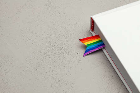 Book with bookmark and rainbow ribbon of LGBT pride.