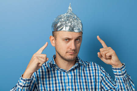 Man with a serious face shows a finger at a cap with aluminum foil. Protects from reading think Stock Photo