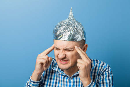Foil hat on man. Man closed his eyes. Protects from reading think