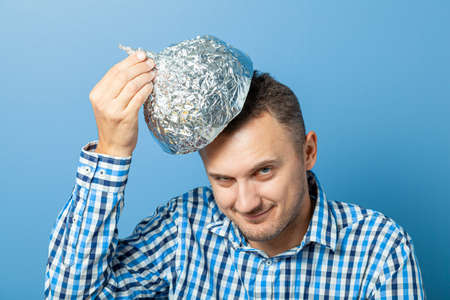Man puts on a helmet made of aluminum foil with pleased face.. Protects from reading think