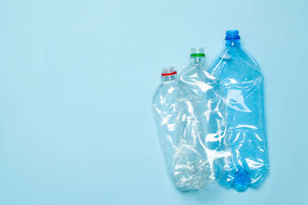 Crumpled plastic bottles on a blue background. Plastic trash. Copy space for text.