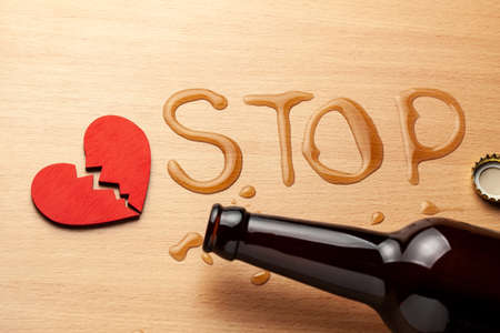 Alcoholism in the family. Broken heart, broken relationship. Beer bottle and spilled beer in the word STOP and heart with a crack Banque d'images