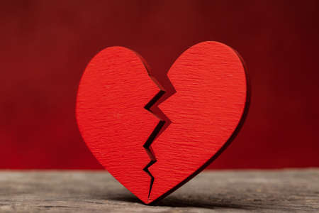 Broken heart. Crack in the red heart, Breaking the relationship. Red background