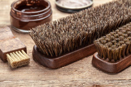 Brush for shoes. Cleaning and polishing shoes with brushes. Shoe polish and brush on wooden background