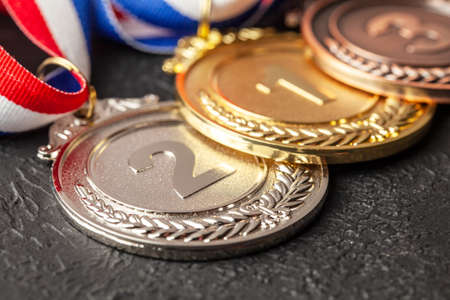 Gold, silver and bronze medal with ribbons. Award for first, second and third place in the competition. Prize to the champion. Black background
