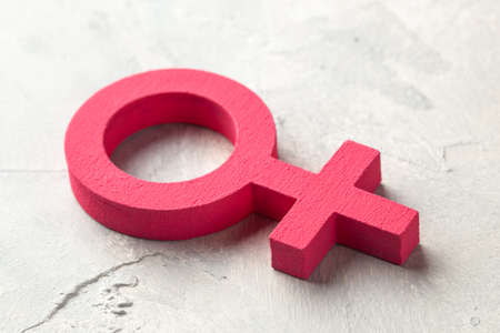 Gender symbols of a woman of pink color on a gray background