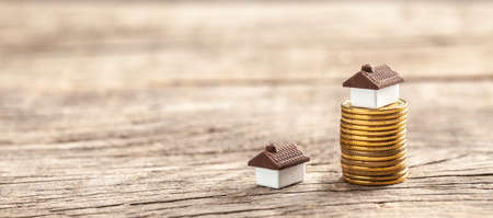 House and a stack of coins. The market price of the house. Real estate market growth.