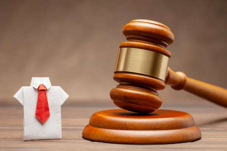 Businessman in shirt and tie and judge gavel on brown background. Concept of business sentence or condemnation of businessman