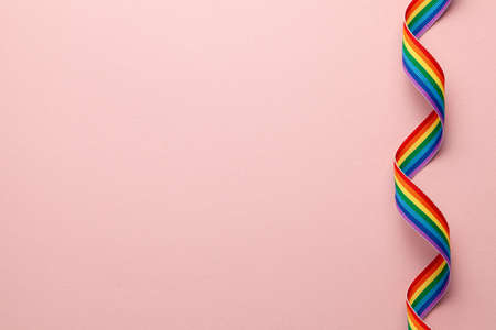 LGBT rainbow ribbon pride tape symbol. Pink background. Copy space for text.