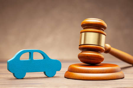 Car and judge gavel on brown background. Concept of selling a car by auction or accident sentence Фото со стока