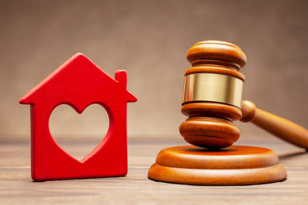 House and judge gavel on brown background. The concept of selling a home cher auction or property section