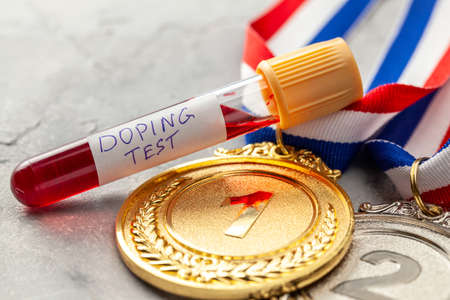 Doping test. Gold, silver and bronze medal and test tube with blood on a gray background Фото со стока
