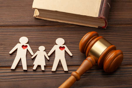 Adoption of a child by a same-sex couple. Judge gavel and the figures of two gay guys with a child hold hands Фото со стока