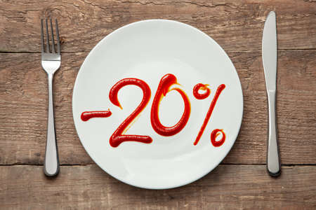 20 discount on food. Food sale. Plate with the inscription ketchup and fork with knife Фото со стока
