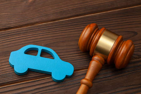 Selling or buying a car at auction. The verdict on a car accident, court. Blue car and judge gavel
